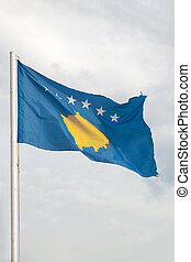 Flag of Kosovo on a blue sky with clouds background
