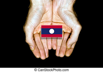 Flag of Laos in hands on black background