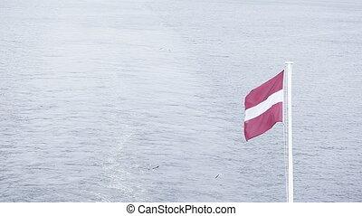 Flag of Latvia - On flagpoles waving Flag of Latvia