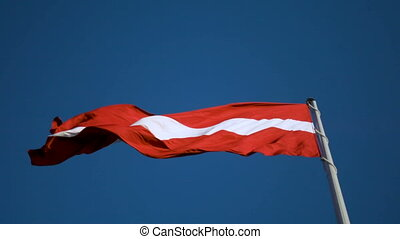 Flag of Latvia on huge high flagpole blowing in the wind