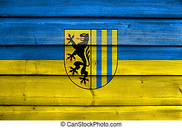 Flag of Leipzig, Germany, painted on old wood plank background