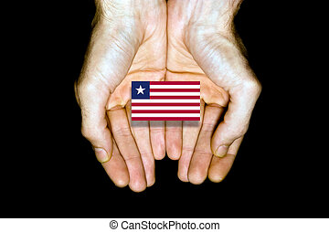 Flag of Liberia in hands on black background