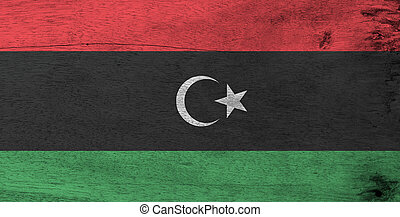 Flag of Libya on wooden plate background. Grunge Libyan flag texture, red black and green with a white crescent and star.