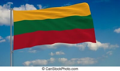 Flag of Lithuania against background of clouds floating on the blue sky