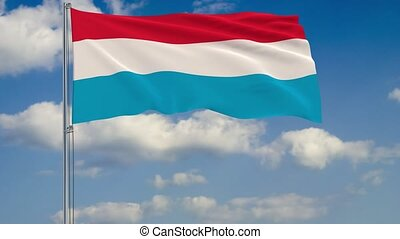 Flag of Luxembourg against background of clouds
