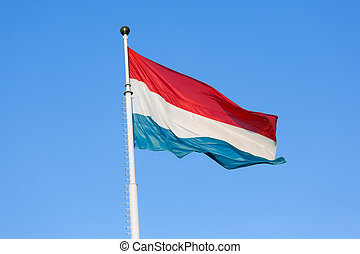 Flag of Luxembourg waving in the wind against blue sky