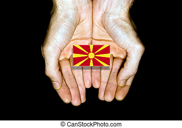 Flag of Macedonia in hands on black background