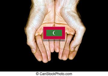 Flag of Maldives in hands on black background