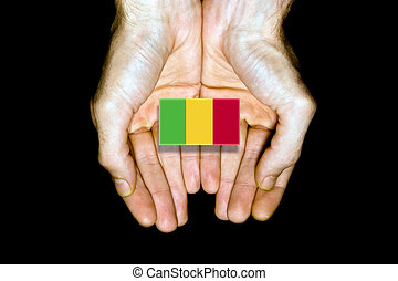 Flag of Mali in hands on black background
