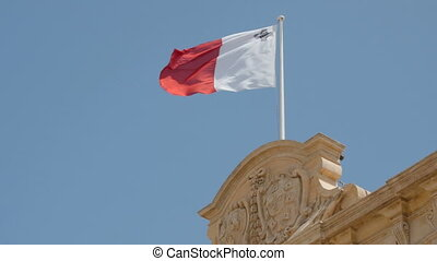 Flag of Malta in front of blue sky floating on flag pole. 4K footage.