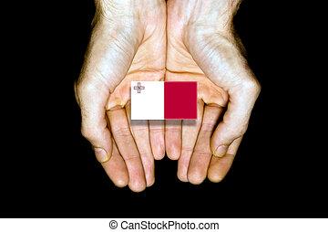 Flag of Malta in hands on black background