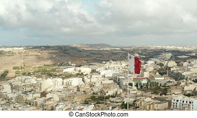 Flag of Malta waving in Wind with view of City on Gozo Island, Aerial Close up slide left