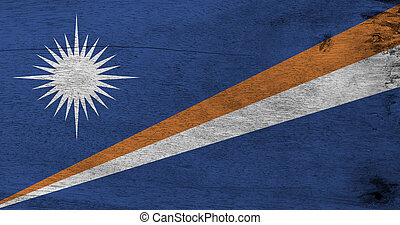 Flag of Marshall Islands on wooden plate background. Grunge Marshall flag texture, A blue field with two diagonal stripes of orange and white and the large white star.