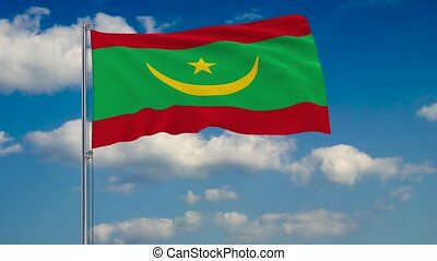 Flag of Mauritania against background of clouds floating on the blue sky