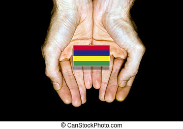 Flag of Mauritius in hands on black background