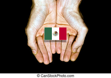 Flag of Mexico in hands on black background