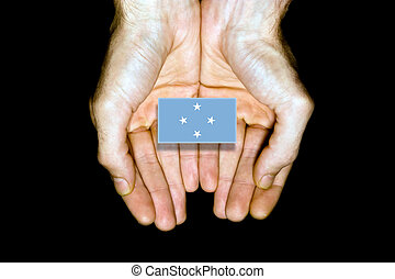Flag of Micronesia in hands on black background