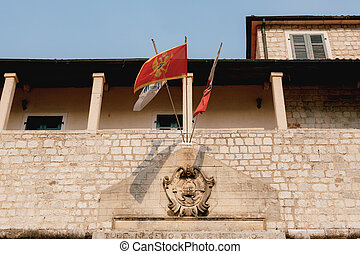Flag of Montenegro above the main gate in the city of Kotor on a flagpole, in an old brick building, near a balcony with columns.