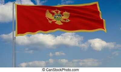 Flag of Montenegro against background of clouds floating on the blue sky