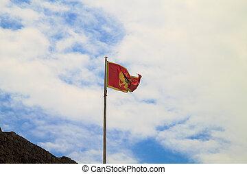 Flag of Montenegro against blue sky