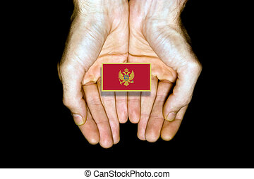 Flag of Montenegro in hands on black background