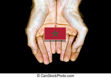 Flag of Morocco in hands on black background