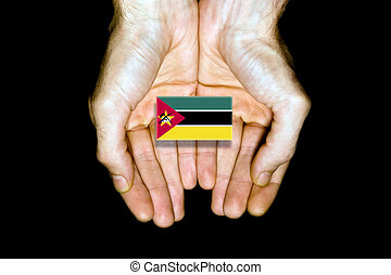Flag of Mozambique in hands on black background