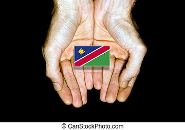 Flag of Namibia in hands on black background