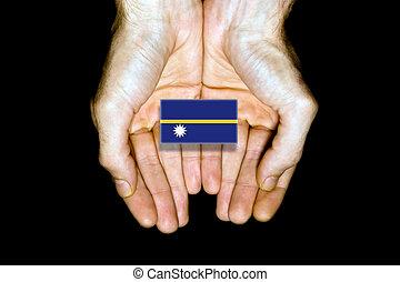 Flag of Nauru in hands on black background