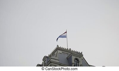 Flag of netherlands on the top of building in front of the...