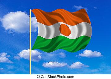 Flag of Niger waving on blue sky background