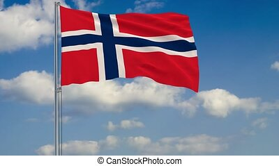 Flag of Norway against background of clouds floating on the blue sky