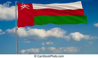 Flag of Oman against background of clouds floating on the blue sky