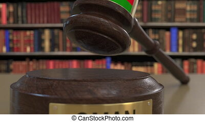 Flag of Oman on falling judges gavel in court. National...