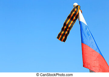 Flag of Russia with St. George's ribbon against the background of a clear cloudless blue sky on the Victory Day on May 9.