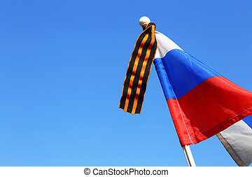 Flag of Russia with St. George's ribbon against the background of a clear cloudless blue sky on the Victory Day on May 9. The Symbol of Victory in the Great Patriotic War.