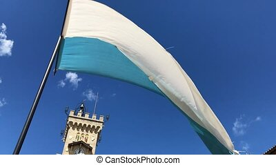 Flag of San-Marino fluttering in the wind with blue sky on the background