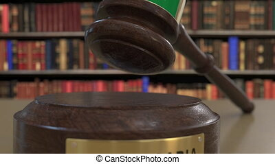 Flag of Saudi Arabia on falling judges gavel in court....