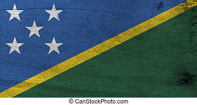 Flag of Solomon Islands on wooden plate background. Grunge Solomon Islands flag texture, A thin yellow narrow diagonal stripe divided diagonally with green and blue triangle and star.