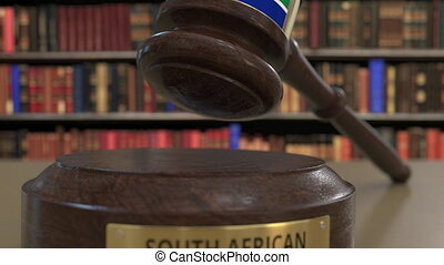 Flag of South Africa on falling judges gavel in court....