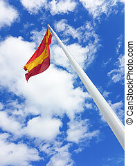 Flag of spain on a mast with sky and clouds