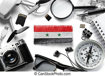 Flag of Syria and travel accessories on a white background.