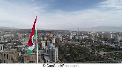 Flag of Tajikistan on flagpole against the blue sky