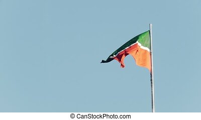Flag of Tatarstan flutters in the wind in front of blue sky,...