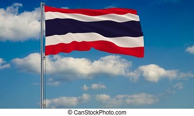 Flag of Thailand against background of clouds floating on the blue sky