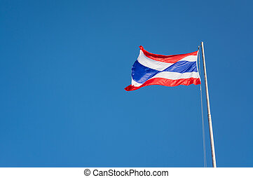Flag of Thailand with clear blue sky.