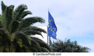 Flag of the European Union waving in the wind on blue backgound among green palm trees.