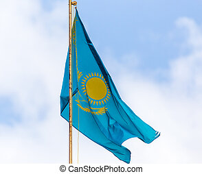 Flag of the Republic of Kazakhstan against the sky with clouds .