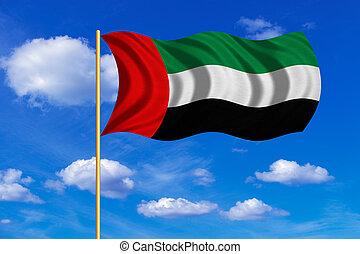 Flag of the UAE waving on blue sky background