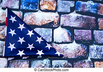 Flag of the United States of America folded in a triangle on a brick wall background